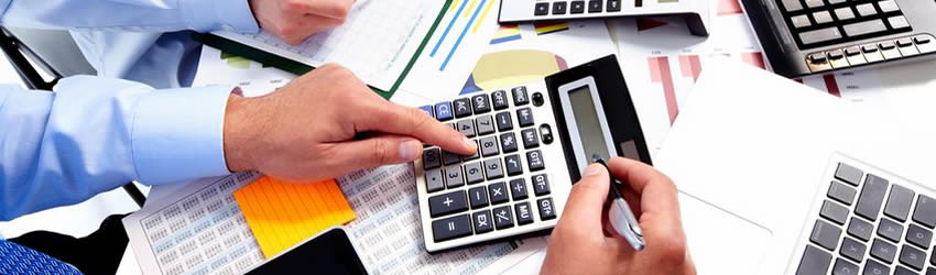 Accountant with calculator and financial documents on desk