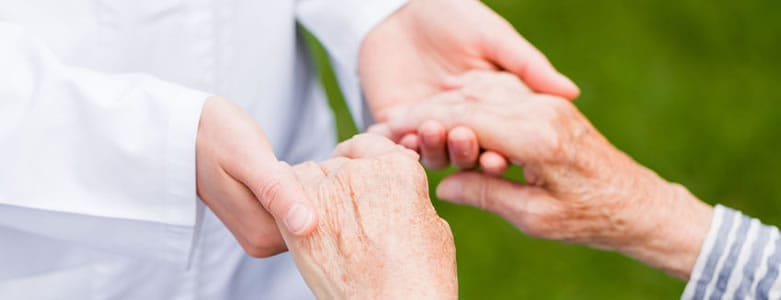 Home health nurse holding hands with patient after being dispatched to home