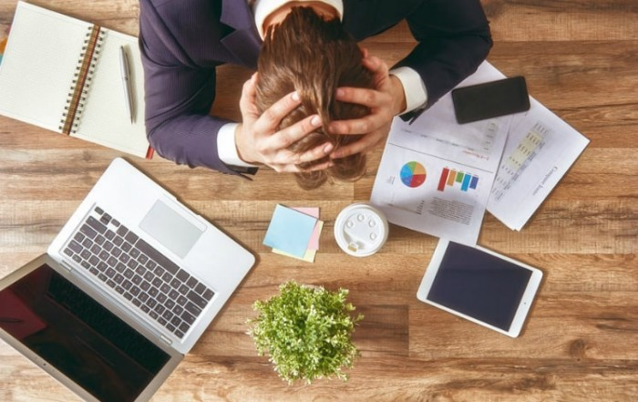 Image of frustrated HR manager with head in hands over issues with employee time and attendance tracking