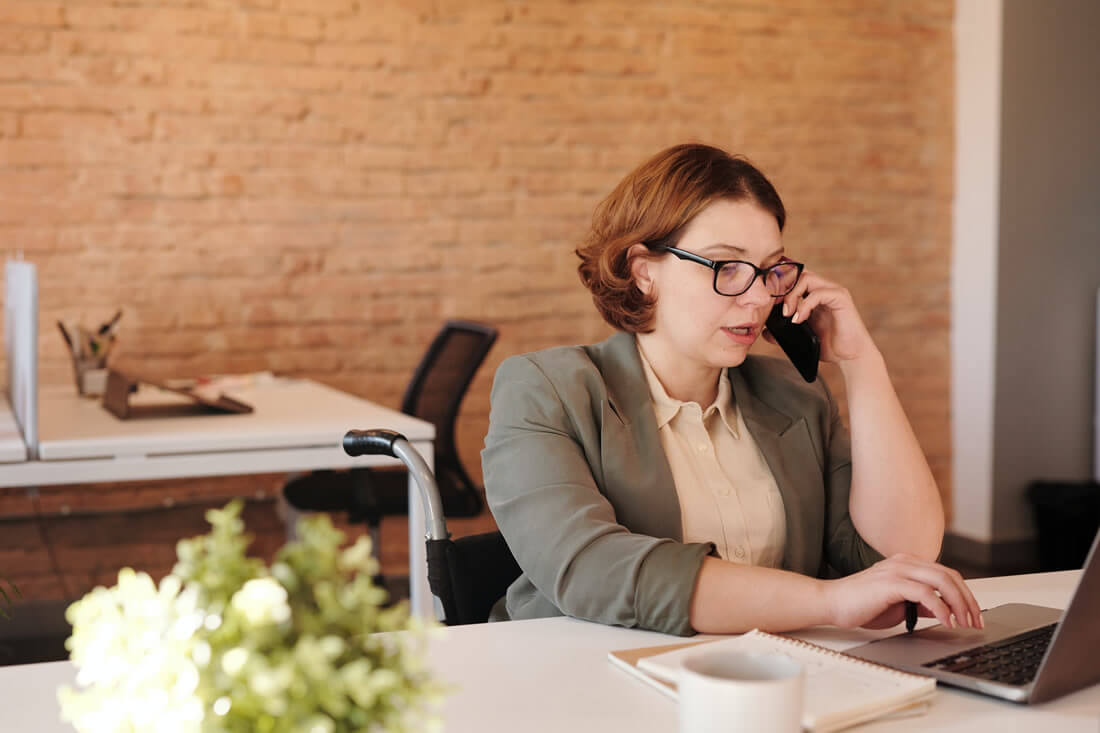 Professional woman on phone in brick wall office