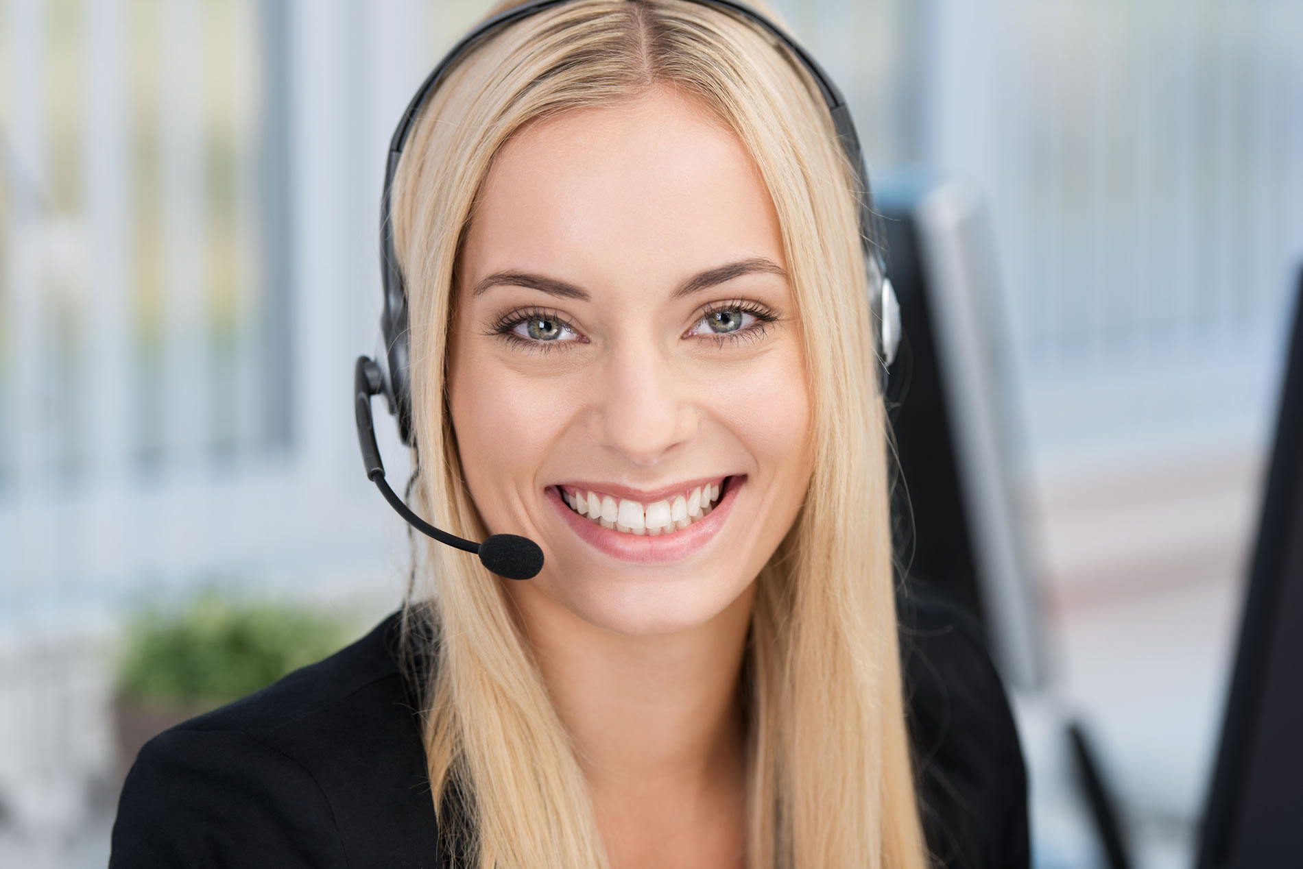 Answering service agent smiling with her headset on before taking a call